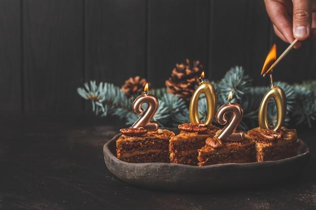 Nowy Rok 2020. świąteczny Tort Ze świecami Na Ciemnym Stole, Miejsce. Premium Zdjęcia