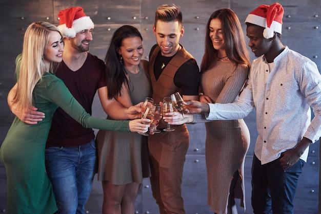 Nowy rok się zbliża! grupa rozochoceni młodzi wieloetniczni ludzie w santa kapeluszach na przyjęciu, pozuje emocjonalnego stylu życia pojęcia ludzi Premium Zdjęcia