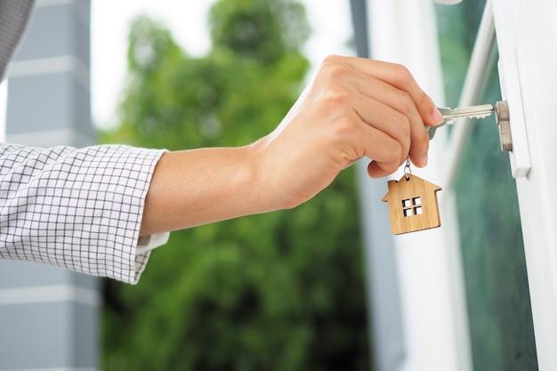 Nowy właściciel otwiera drzwi do domu. Premium Zdjęcia