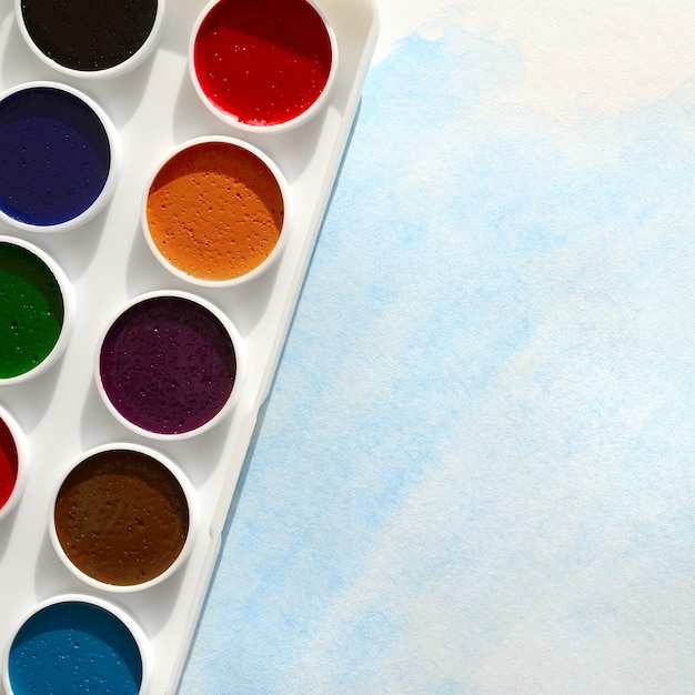 Nowy zestaw akwarel leży na kartce papieru, która pokazuje abstrakcyjny rysunek akwareli Premium Zdjęcia