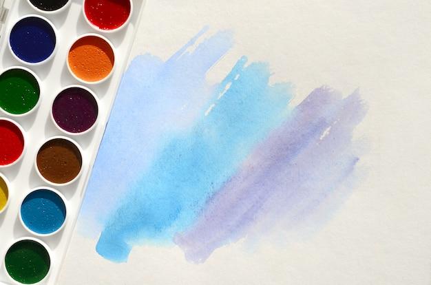 Nowy zestaw akwarel leży na kartce papieru, która pokazuje abstrakcyjny rysunek w akwarela w postaci niebieskich pociągnięć Premium Zdjęcia