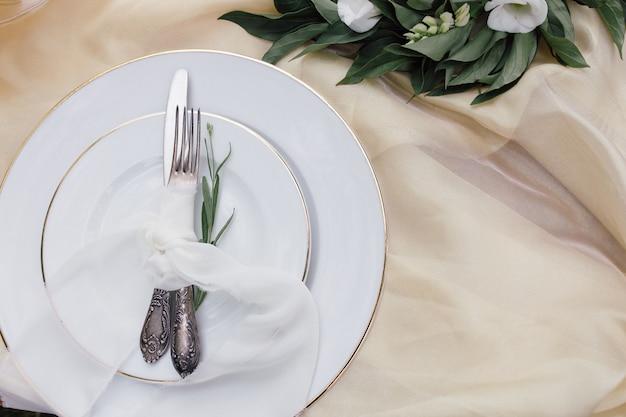 Nóż, Biały Talerz I Widelec Na Beżowym Obrusie Premium Zdjęcia