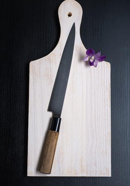 Nóż Do Sushi Na Białej Drewnianej Desce, A Obok Niego Orchidea Premium Zdjęcia