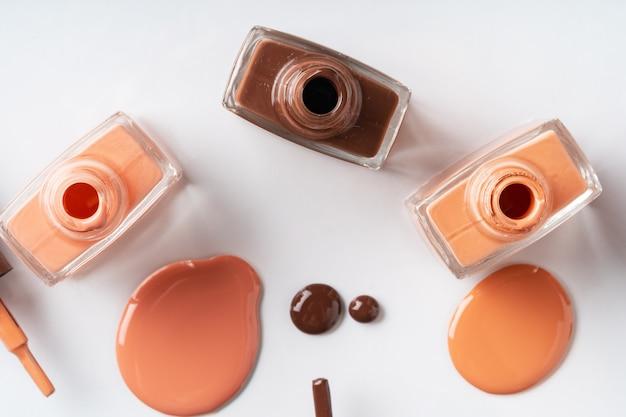 Nude kolory lakier do paznokci rozlane na białym tle Premium Zdjęcia