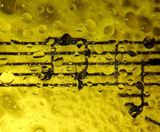 Nuty na szkle zalane kroplami z żółtym tłem Premium Zdjęcia