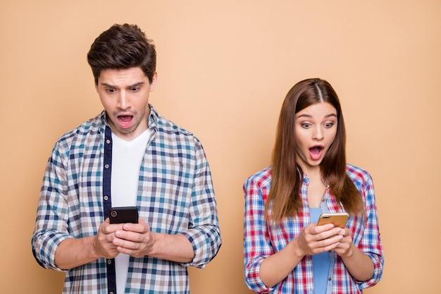 O Mój Boże! Portret Współmałżonków Pod Wrażeniem Blogerzy Przeglądają Smartfony Otrzymuj Powiadomienia Z Sieci Społecznościowej Czuć Otępienie Wpatrując Się W Ekran Nosić Kraciasty Swobodny Strój Izolowany Na Pastelowym Tle Premium Zdjęcia