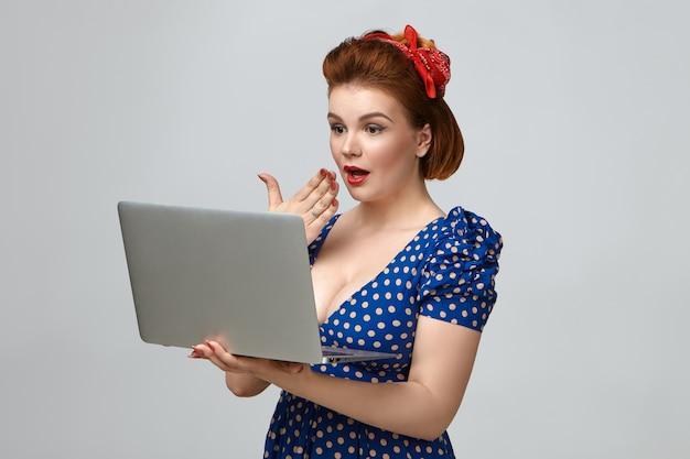 O Mój Boże. Strzał Studio Wspaniałej Emocjonalnej Młodej Damy W Stroju Vintage, Trzymając Typowy Laptop, Mając Zaskoczony Wyraz Twarzy, Trzymając Dłoń Na Ustach Darmowe Zdjęcia