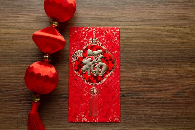 Obchody Chińskiego Nowego Roku I Nowego Roku Księżycowego Ze Złotym Sztabką W Postaci Czerwonej Koperty I Gorącej Herbaty. Chińskie Słowo Oznacza: Błogosławieństwo, Szczęście I Szczęście Premium Zdjęcia