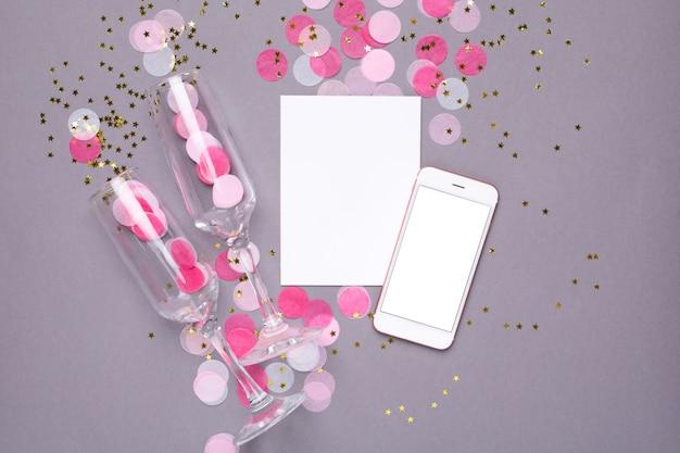 Obecna karta, makieta telefonu komórkowego i różowe konfetti ze złotymi gwiazdkami na szaro Premium Zdjęcia