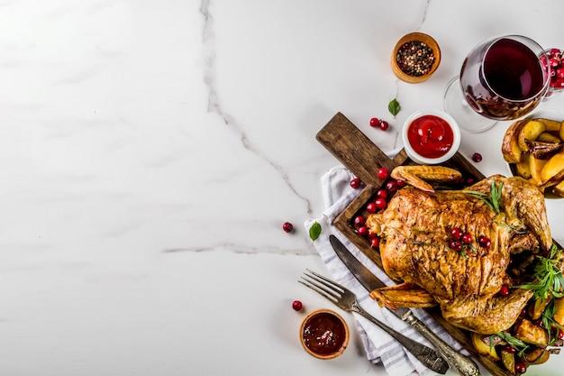 Obiad Dziękczynienia, Pieczony Pieczony Kurczak Z żurawiną I Ziołami, Podawany Ze Smażonymi Warzywami, Winem Ze świeżych Jagód I Sosami Na Stole Z Białego Marmuru, Widok Z Góry Premium Zdjęcia