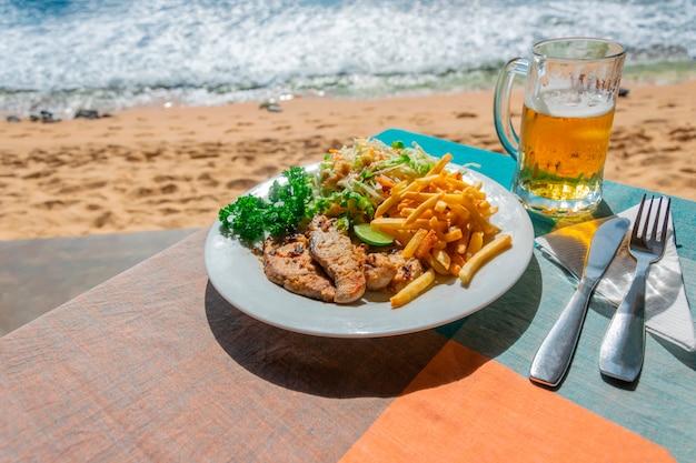Obiad W Kawiarni Na świeżym Powietrzu Nad Morzem Lub Oceanem. Plastry Smażonej Ryby I Frytek Z Surówką Z Kapusty I Szklanką Zimnego Jasnego Piwa Premium Zdjęcia