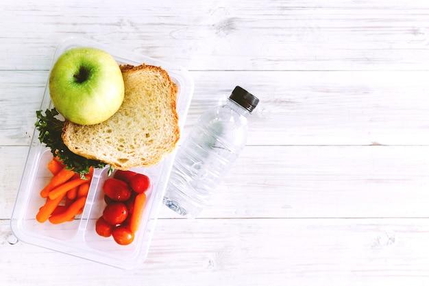 Obiadowy pudełko z warzywami i plasterkiem chleb dla zdrowego szkolnego lunchu na drewnianym stole Premium Zdjęcia