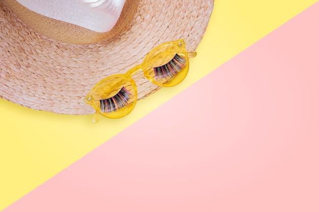 Obiekty Chroniące Przed Słońcem. Słomiany Kobieta Kapelusz Z Okularów Przeciwsłonecznych I Sfałszowanych Rzęs Widoku Z Góry Tła Jaskrawego żółtego Mieszkania Nieatutowym Singlem. Premium Zdjęcia