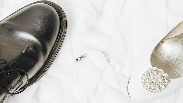 Obrączki ślubne między białymi szpilkami i czarnymi butami na szaliku Darmowe Zdjęcia