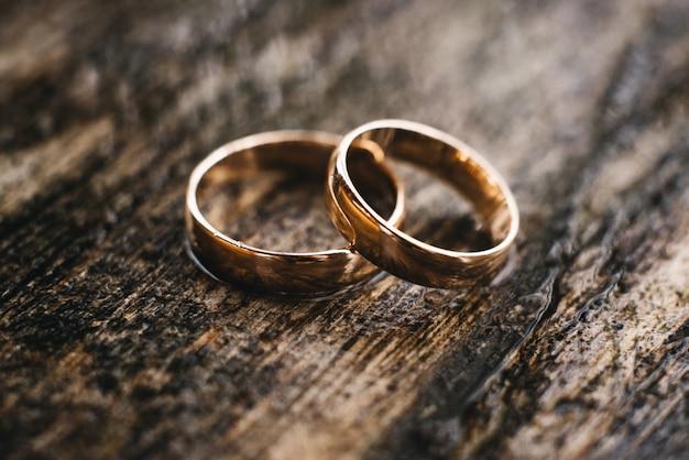 Obrączki ślubne Na Pięknej Drewnianej Teksturze Ukazują Się Zbliżenie Premium Zdjęcia