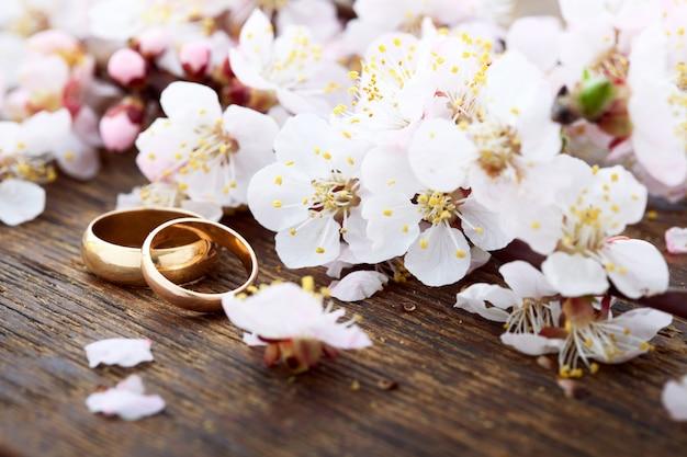 Obrączki ślubne. Wiosna. Kwitnąca Gałąź Na Drewnianej Powierzchni. Premium Zdjęcia