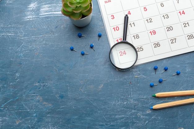 Obraz biznesu i spotkań. kalendarz przypominający o ważnym spotkaniu i lupę Premium Zdjęcia