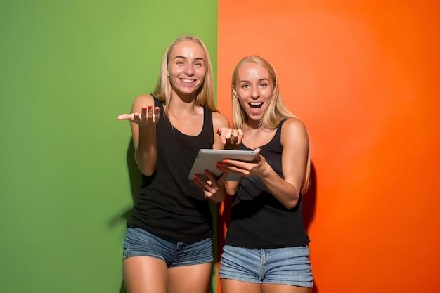 Obraz Dwóch Młodych Szczęśliwych Kobiet Patrząc W Kamerę I Trzymając Laptopy W Studio. Darmowe Zdjęcia