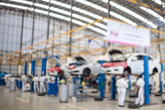 Obraz Jest Niewyraźny, Gdy Mechanik Pracuje W Centrum Serwisowym Samochodu. Są Samochody. Wielu Klientów Korzysta Z Usługi Wymiany Oleju. Premium Zdjęcia