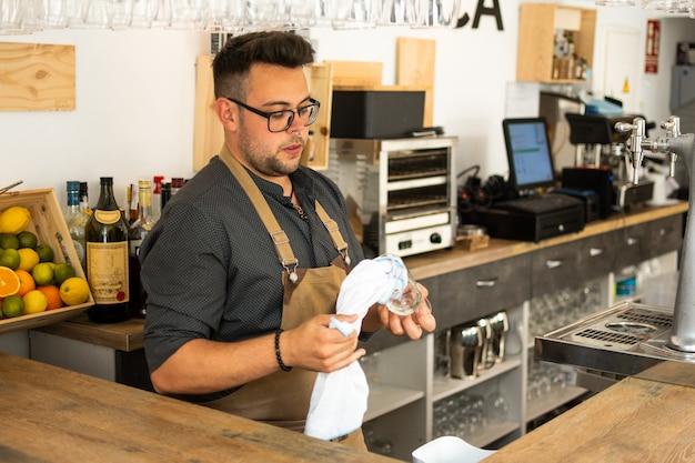 Obraz kelner czyszczenia kieliszek do wina w pubie. zawód, koncepcja stylu życia, praca. Premium Zdjęcia