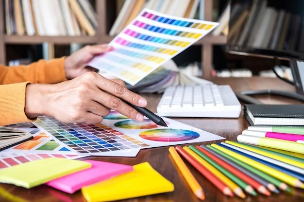 Obraz kreatywnego projektanta graficznego pracy nad wyborem koloru i rysunek na tablecie graficznym Premium Zdjęcia
