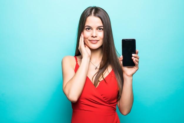 Obraz ładny Całkiem Młoda Dama Na Białym Tle Nad Niebieską ścianą. Pokazujący Wyświetlacz Telefonu Komórkowego. Darmowe Zdjęcia