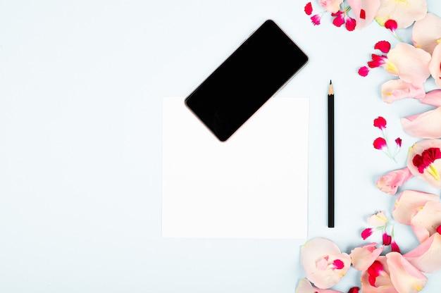 Obraz Na Blogu Dla Kobiet. Mieszkanie Leżało Z Kwiatami, Notatnikiem, Smartfonem I Ołówkiem Na Tle Papieru Premium Zdjęcia