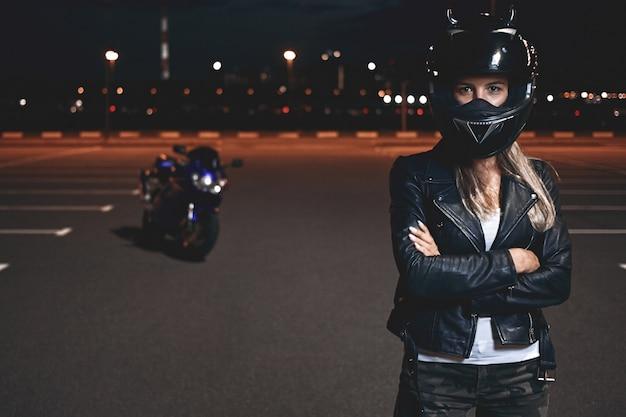 Obraz Pewnej Siebie, Zdeterminowanej, Młodej Jeźdźca W Kasku Ochronnym Stojącej Na Parkingu, Trzymającej Ręce Skrzyżowane I Patrząc, Jadącej Na Motocyklu Po Mieście Nocą Darmowe Zdjęcia