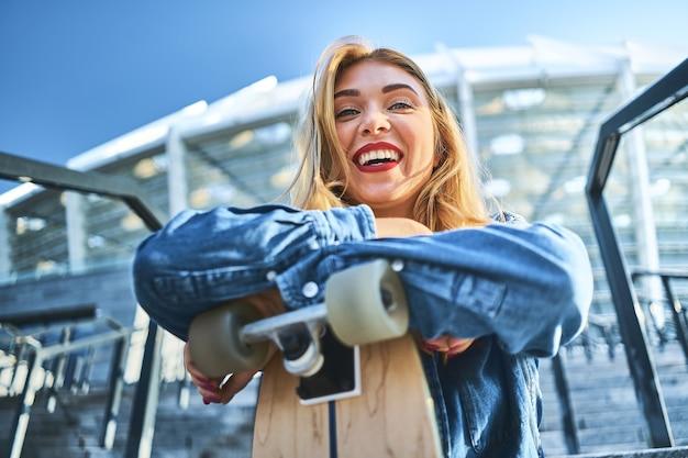 Obraz Piękna Stylowa Uśmiechnięta Kobieta Siedzi Na Schodach Ulicy W Letni Dzień I Trzyma Deskorolkę. Premium Zdjęcia