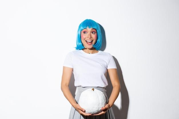 Obraz Podekscytowanej ślicznej Azjatyckiej Dziewczyny Patrzącej Na Baner W Lewym Górnym Rogu O Halloween, Trzymający Białą Dyni, Ubrany W Niebieską Perukę Na Imprezę. Darmowe Zdjęcia