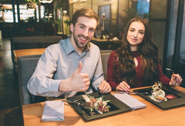 Obraz Reklamowy Mężczyzny I Kobiety Siedzącej Przy Stole Z Jedzeniem. Patrzą W Kamerę I Uśmiechają Się. Mężczyzna Pokazuje Swój Duży Kciuk Do Góry. Premium Zdjęcia