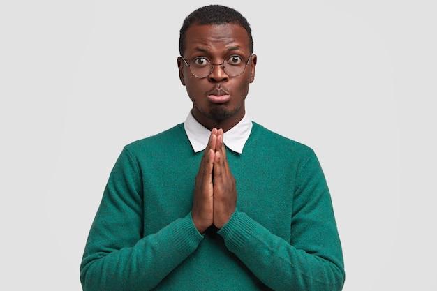 Obraz Smutnego, Ponurego Afroamerykanina Trzyma Dłonie Razem, Prosi O Pomoc Bliskiego Przyjaciela, Zaciska Dolną Wargę, Ma Ciemną, Zdrową Skórę Darmowe Zdjęcia