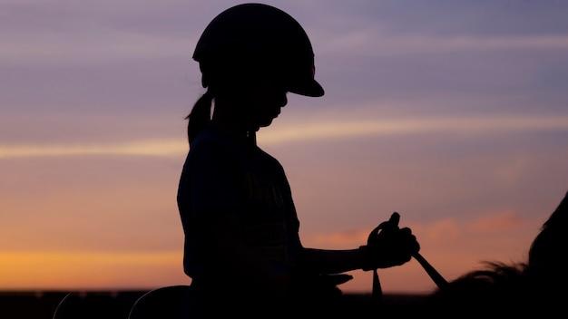 Obraz Sylwetka Szkoły Dziecko Dziewczyna Jedzie Na Koniu Ponowniets Zmierzch Niebo. Premium Zdjęcia