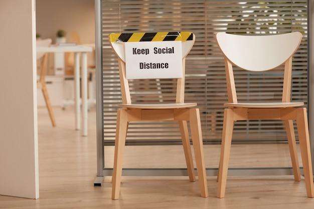 Obraz W Tle Drewnianych Krzeseł Do Oczekiwania W Kolejce W Biurze Ze Znakiem Keep Social Distance, Kopia Przestrzeń Premium Zdjęcia