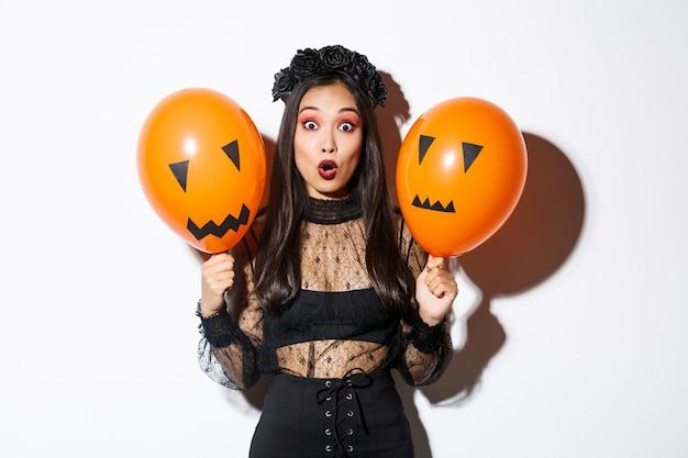 Obraz Zdziwionej Azjatki W Stroju Czarownicy świętującej Halloween, Trzymającej Balony Z Przerażającymi Twarzami Darmowe Zdjęcia