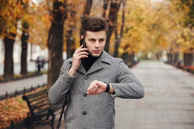 Obrazek Eleganckiego Mężczyzna Sprawdza Czas Z Zegarkiem Na Ręce I Mówi Na Telefonie Komórkowym Podczas Jego Spaceru W Parku Darmowe Zdjęcia