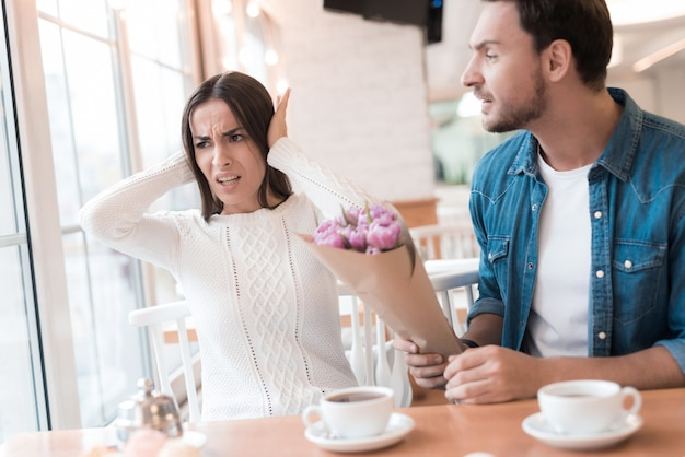 Obrażony mężczyzna dziewczyna z kwiatami kłótni w kawiarni. Premium Zdjęcia