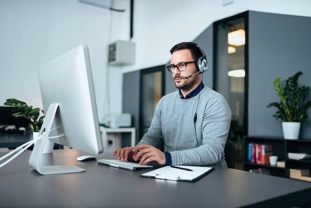 Obsługa Klienta Młodych Mężczyzn Z Zestawem Słuchawkowym Działającym Na Komputerze. Premium Zdjęcia