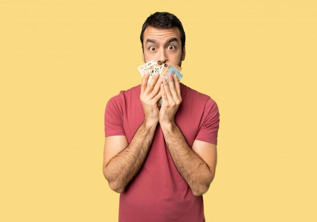 Obsługuje brać dużo pieniądze zakrywa usta z rękami dla mówić coś niestosownego na odosobnionym żółtym tle Premium Zdjęcia