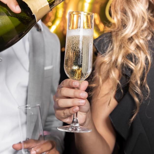 Obsługuje dolewanie szampana w szkle trzymającym kobiety zakończeniem Darmowe Zdjęcia