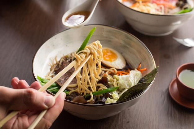 Obsługuje jeść azjatyckich ramen z tuńczykiem i kluskami w restauraci Premium Zdjęcia