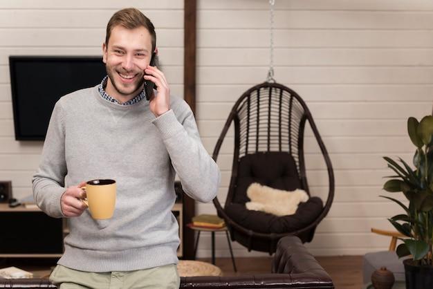 Obsługuje Mienie Kubek I Opowiadać Na Telefonie W Domu Darmowe Zdjęcia