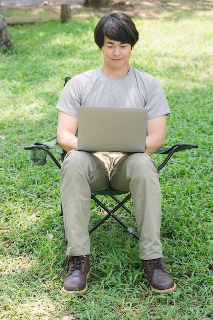 Obsługuje Obsiadanie Na Campingowym Krześle I Działanie Z Laptopem W Ogródzie Premium Zdjęcia