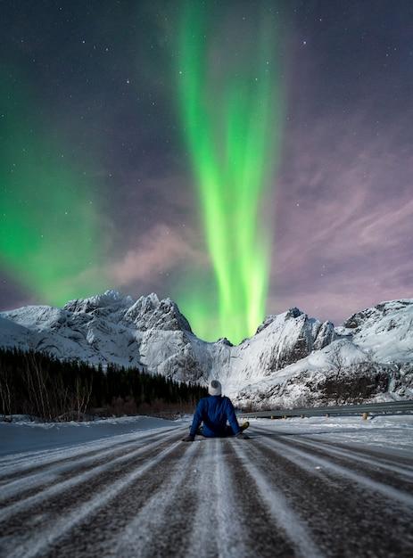 Obsługuje Obsiadanie Na śnieżnej Drodze Patrzeje Północnych światła Premium Zdjęcia