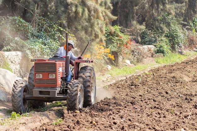 Obsługuje Przygotowywać Ziemię Dla żniwa Z Ciągnikiem Na Gospodarstwie Rolnym Premium Zdjęcia