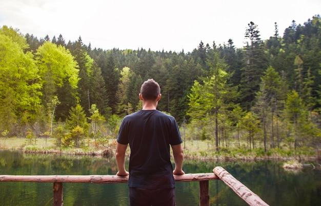 Obsługuje samotną pozycję i patrzeć na zdewastowanym jeziorze w lesie. Premium Zdjęcia