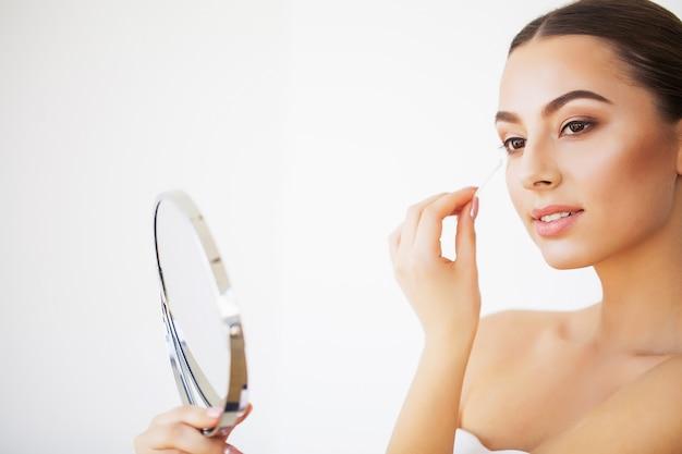 Ochrona skóry. portret seksowna młoda kobieta patrzeje w lustrze indoors z świeżą zdrową skórą Premium Zdjęcia