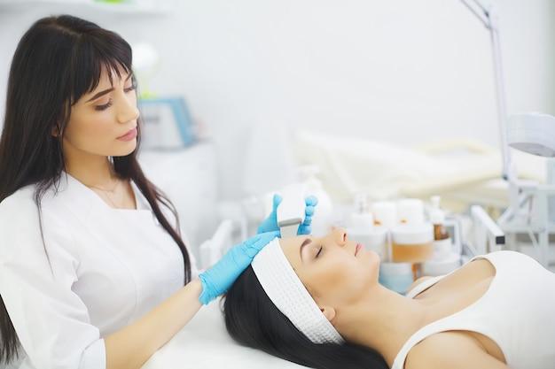 Ochrona skóry. zakończenie piękna kobieta otrzymywa ultradźwiękowego kawitacja peeling twarzy. procedura ultradźwiękowego oczyszczania skóry. zabieg upiększający. kosmetyka. beauty spa salon. Premium Zdjęcia