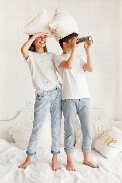 Oczu Osłaniając Dziewczynę Stojącą Na łóżku Z Bratem Patrząc Przez Teleskop Darmowe Zdjęcia