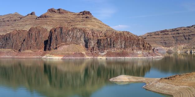 Odbicie Skalistych Klifów W Jeziorze Pod Niebieskim Niebem Darmowe Zdjęcia